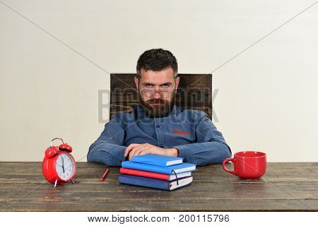 Exam and studying concept. Man with moody or serious face sits at wooden table. Cup retro clock with red and blue books on vintage table. Examiner with beard and glasses isolated on white background