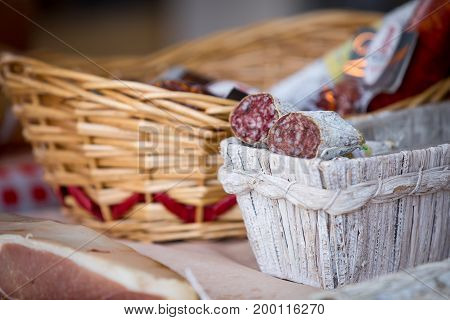 Traditional home-made salami in the basket on the market for sale.. The production of sausages