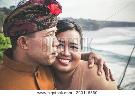 Close Up Portrait Of Lovely Honeymoon Balinese Couple In Traditional Clothes Together In Nature. Bal