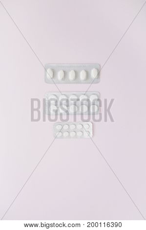 Flat lay medicine pills on pink background. Top view medical texture.