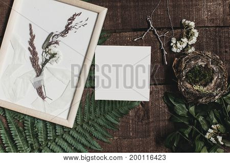 Wedding Invitation Mock-up And Rustic Boutonniere Under Glass Frame On Wooden  Background With Fern