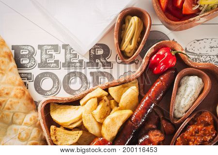 Beer and snack set. Variety of beers, grilled sausages, fried potatoes, salted on wooden background