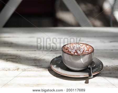 Tasty cappuccino on a gray wooden table background. A close-up picture of a gray porcelain mug full of sweet cacao drink with white marshmallows. A cup with a metal spoon. Copy space.