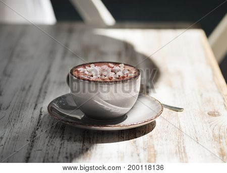 A close-up picture of a gray porcelain mug full of hot chocolate with white marshmallows. Sweet cappuccino on a gray wooden table background. A cup with a metal spoon. Copy space. Breakfast concept.