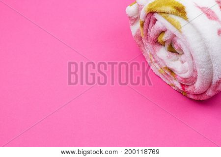 Roll of plaid. Coiled plaid on the pink background