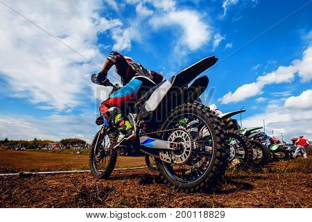 Racer on a motorcycle participates in motocross prepare for the start against a team of rivals. Concept active extreme rest.