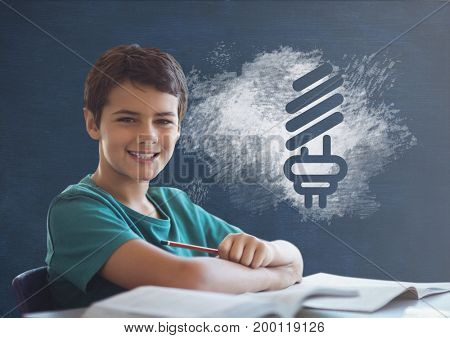Digital composite of Student boy at table against blue blackboard with school and education graphic