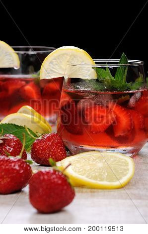 A glass of chilled strawberry lemonade mint leaves a slice of lemon with ice