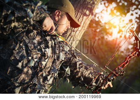 Modern hunter with a bow and arrow hunting in the forest