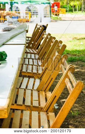 Long tables in garden row of wooden chairs. Preparation for outdoor summer picnic or public fest. Green grass sunlight flecks leisure. Lifestyle image.