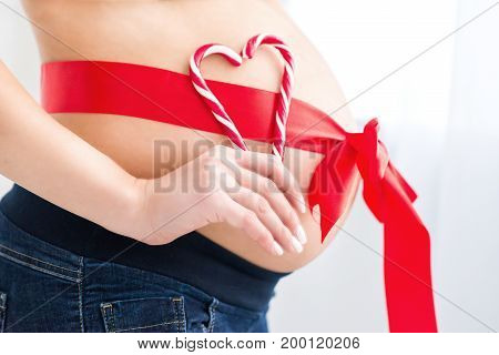 Pregnant belly with red and white heart made of candy. Pregnant belly dressed with a red festive ribbon