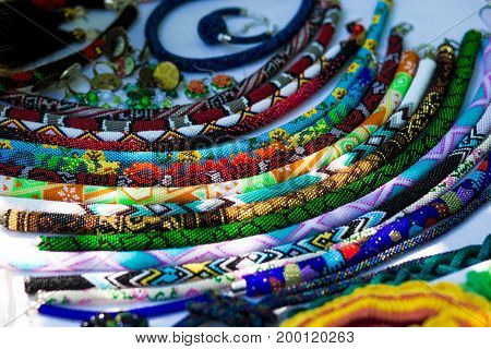 Fashionable handmade accessories for women. Decorative beads necklaces and bracelets. Strands of small colorful beads necklaces