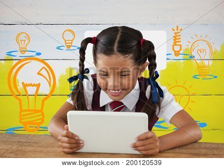 Digital composite of Schoolgirl on tablet with colorful light bulb graphics