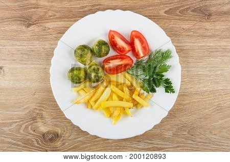 White Dish With Fried Potatoes, Tomatoes, Brussels Sprouts And Greens