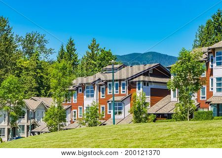 Street of residential townhouses on sunny day with mountain view and blue sky background