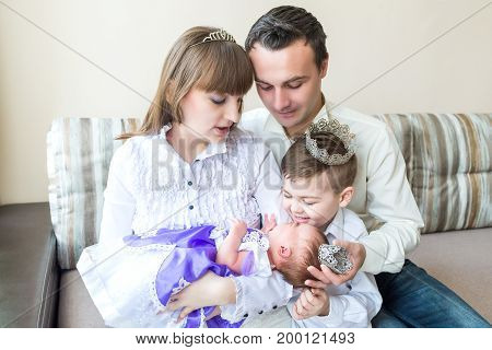 Family sitting on sofa with newborn baby. Mother, father, brother and newborn baby girl princess