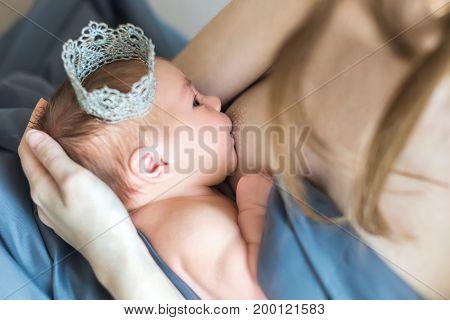 Mother breastfeeding her newborn baby on bed. Newborn baby princess sucking breast