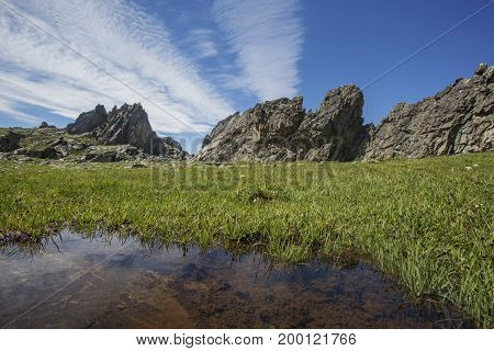 Mountain Altai sunny landscape with rocks and puddle. Russia. Summer nature