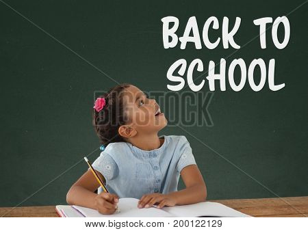 Digital composite of Student girl at table looking up against green blackboard with back to school text
