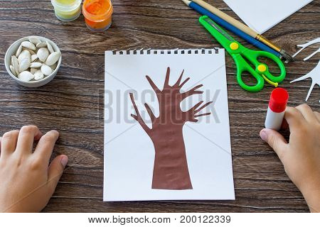 The Child Cuts Out The Details Of The Application. Postcard Autumn Tree With Multi-colored Leaves Of