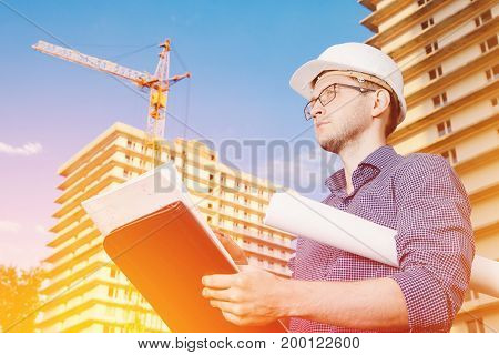 Close-up male construction worker wearing helmet, glasses, shirt in his hands holding folder, papers, blueprints background of construction site: crane, multi-storey building. Looks off-frame
