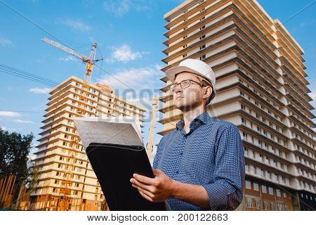 Close-up man builder European wearing helmet, glasses, shirt in his hands holding folder, papers, blueprints background construction site: crane, multi-storey house. Looks construction site