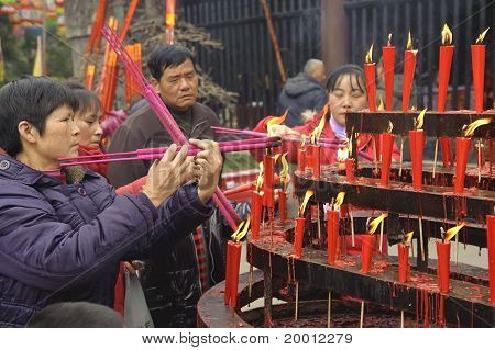 People burning incense upon the incense altar in temple