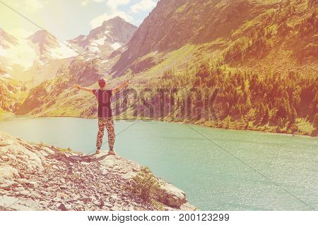 Male Tourist Hiker Stands On A Rock With Raised Hands.