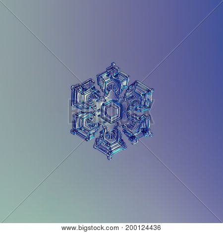 Real snowflake macro photo: star plate snow crystal with short broad arms, small central hexagon, and glossy relief surface, covered by frozen bubbles of rime. Snowflake glittering on blue background.