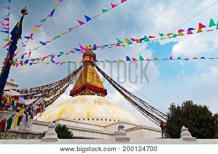 Bodhnath Stupa Temple and praying flag. Boudhanath Stupa (or Bodnath Stupa) is the largest stupa in Nepal and the holiest Tibetan Buddhist temple outside Tibet.