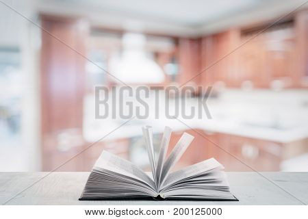 open cookbook on white wooden table in the kitchen