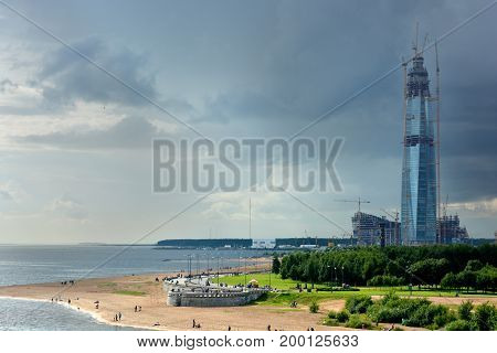 A skyscraper under construction on the seashore under the sky changing from blue to a thunderstorm.