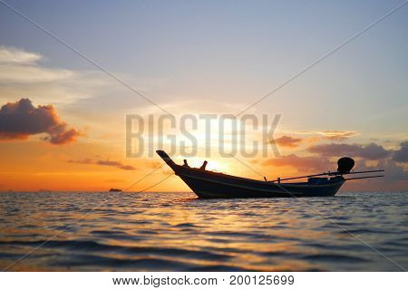 Wooden Thai Long Tail Boat and Golden Sunset at Koh Phangan. Travel, summer, vacation and tropical beach concept