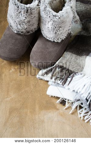 Warm home clothes. Woolen plaid and home slippers on wooden background.