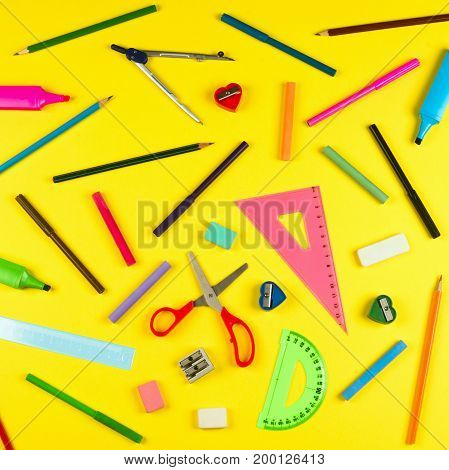 Different school supplies are on yellow background.