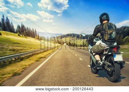Motorcyclist rushes along the picturesque mountain highway. sport bike