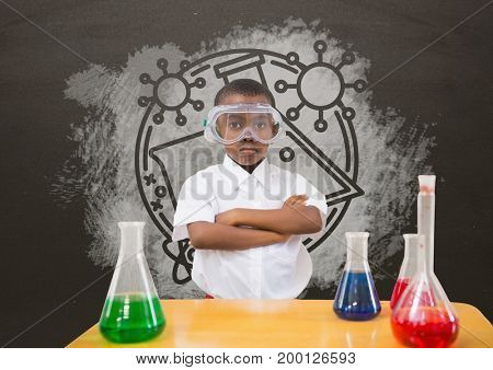 Digital composite of Student boy at table against grey blackboard with school and education graphic