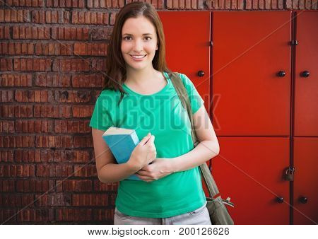 Digital composite of female student holding book in front of lockers