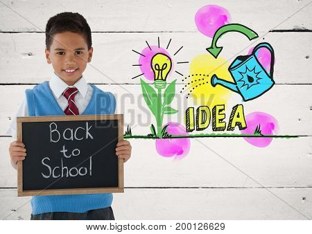 Digital composite of boy holding blackboard with back to school and idea colorful graphics