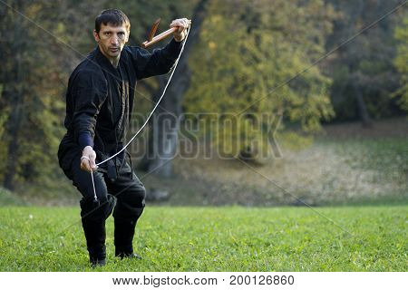 Ninja in black kimono is practicing martial arts with kusarigama outdoors in nature.