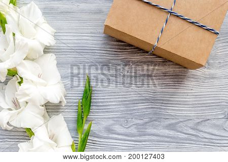 Celebration accessories. Box in kraft paper near flower gladiolus on light wooden table top view.