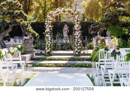 Wedding arch with flowers outdoors. Beautiful wedding set up. Wedding ceremony in the garden with sculptures and fountain. Part of the festive decor, floral arrangement