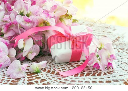 bouquet of sweet peas gift box with ribbon on table near window sunlight holiday greeting