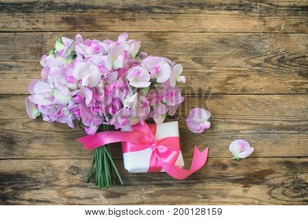 delicate bouquet of sweet peas gift box with ribbon on wooden table vintage style view from above