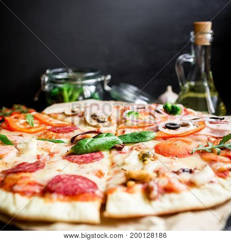 Tasty pizza with ingredients, spices and cutlery on black background.