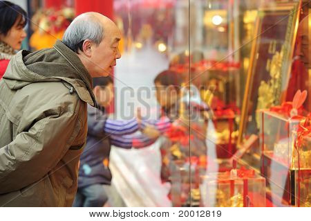 A man stop to look in the window of a gold shop on a busy pedestrian shopping street