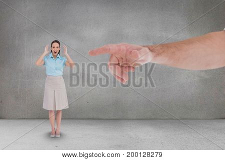 Digital composite of Hand pointing at happy business woman against grey background
