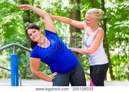 Thin and overweight woman workout together outdoors