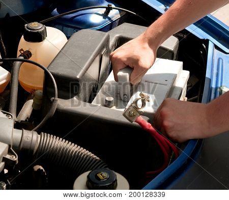 Mechanic changing car battery, closeup shot