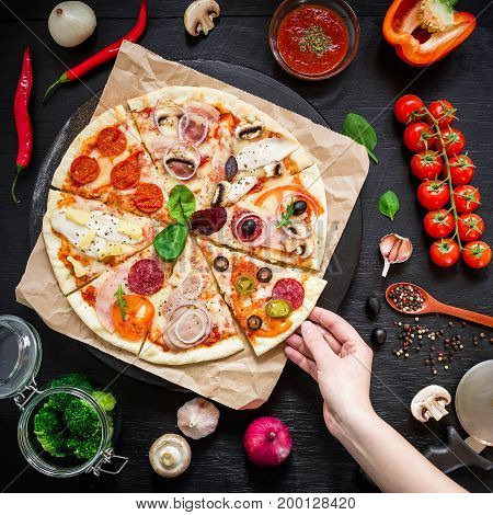 Delicious pizza with ingredients and woman hand on dark table. Flat lay. Top view. Italian food